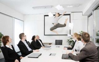 Frau, die enthusiastisch in die Luft springt bei einem Meeting