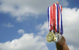 Die drei Medaillen, hochgehalten vor einem blauen Himmel